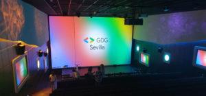Escenario del DevFest. Pantalla gigante con el logo de GDG Sevilla sobre los colores de Google (degradado azul, rojo, verde y amarillo)