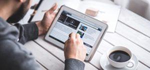 Hombre interactúa con tablet mientras toma un café