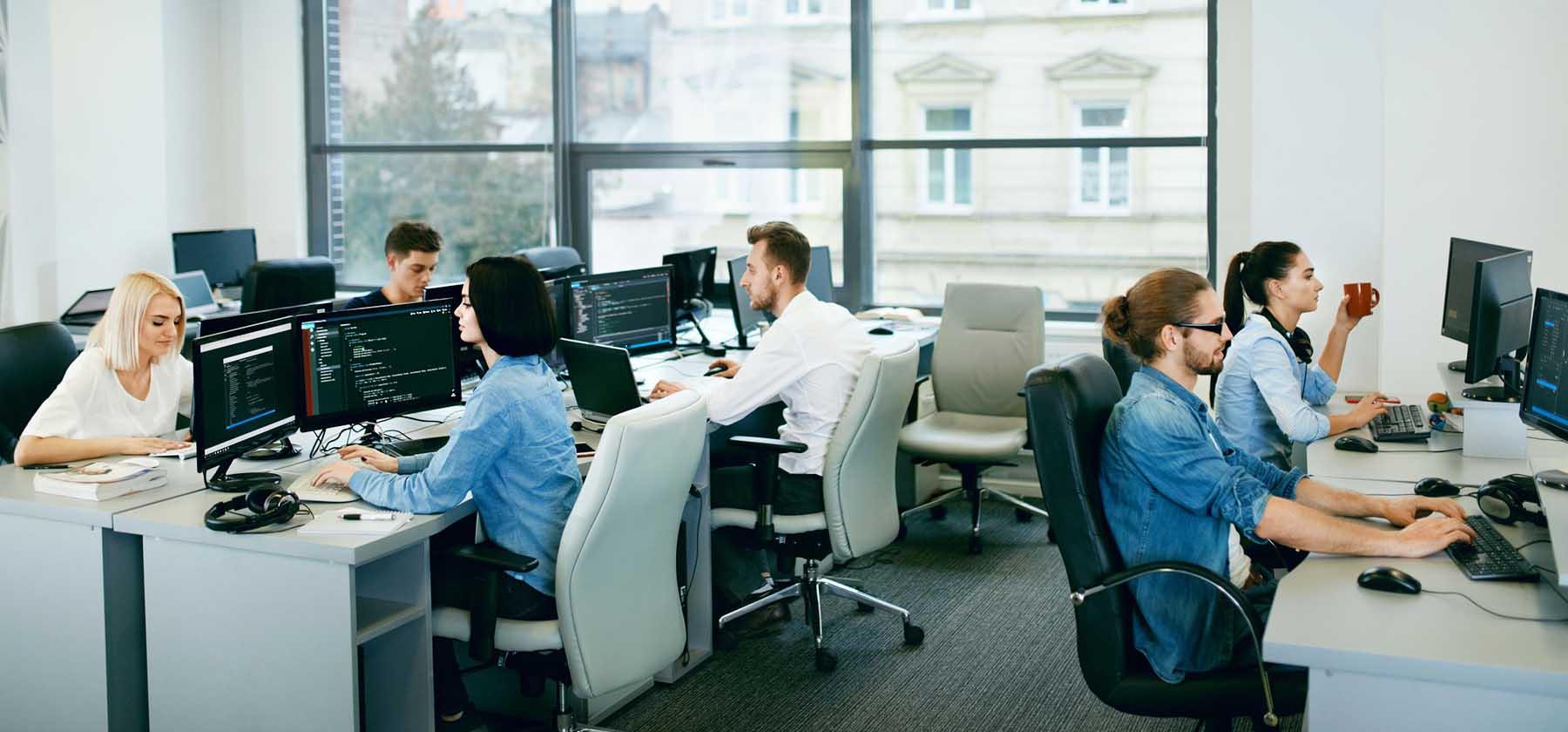 Equipo de diferentes desarrolladores (3) y desarrolladoras (3) trabajando en una oficina,.
