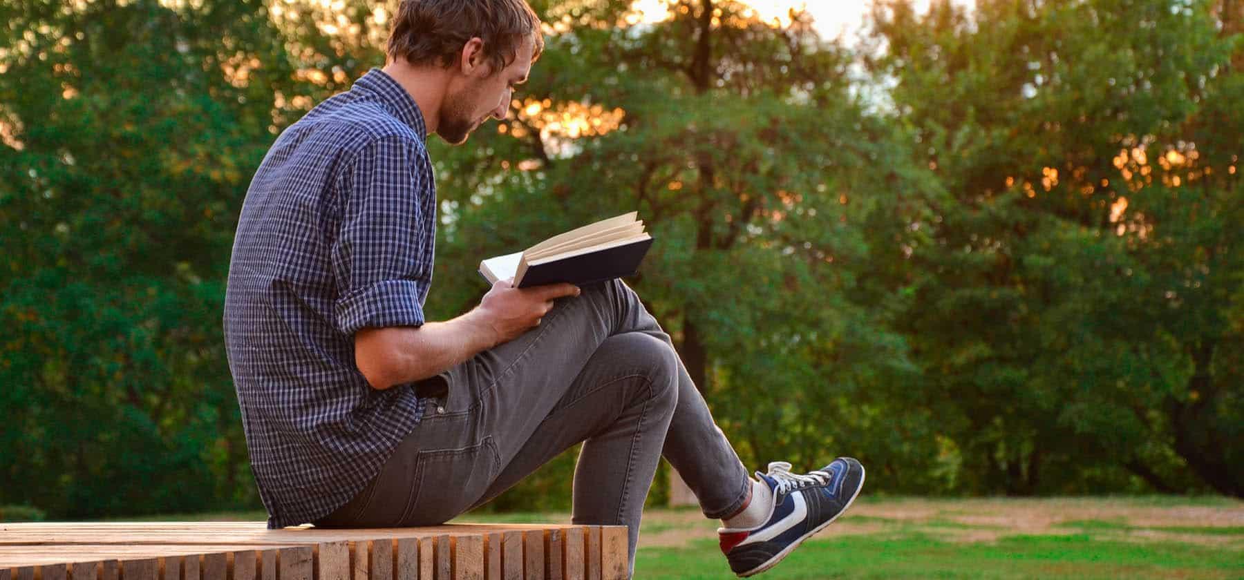 Desarrollador de software leyendo un libro en el bosque